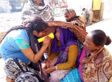 Community Health Worker screening patient's eyes