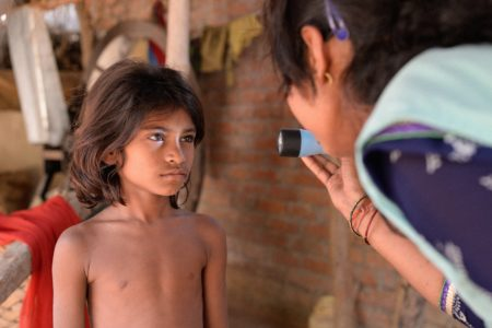 Indian boy having his eyes examined by a community health worker