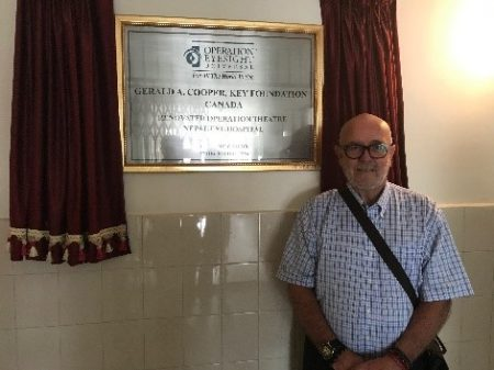 Foster pictured here beside a plaque inaugurating the newly upgraded operating theatre at the Nepal Eye Hospital, made available through gracious donor support.