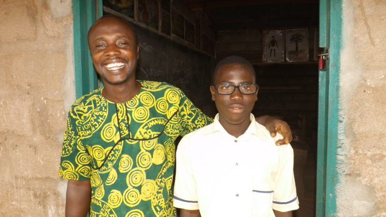 A boy in ghana pictured with his teacher after receiving new prescription eyeglasses to help him see clearly and go back to school